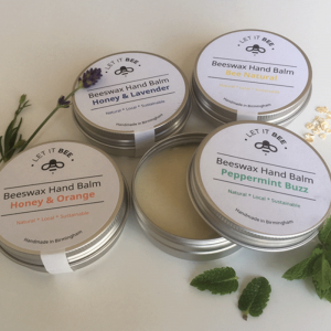 4 tins of Beeswax Hand Balm, one open, with lavender sprig and mint leaves