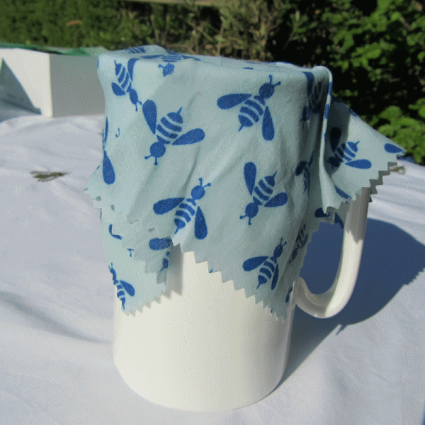 Beeswax Food Wrap covering a large white jug, outdoors