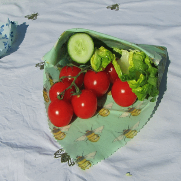 Beeswax Food Wrap with tomatoes, cucumber and lettuce partially inside